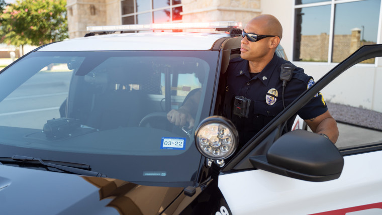 A policeman getting in a police car
